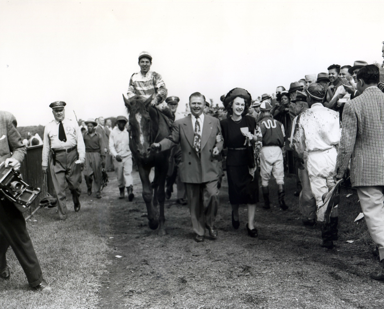 Stymie (Conn McCreary up) being led into the winner's circle by trainer Hirsch Jacobs and owner Ethel Jacobs for the International Gold Cup at Belmont (Keeneland Library Morgan Collection/Museum Collection)