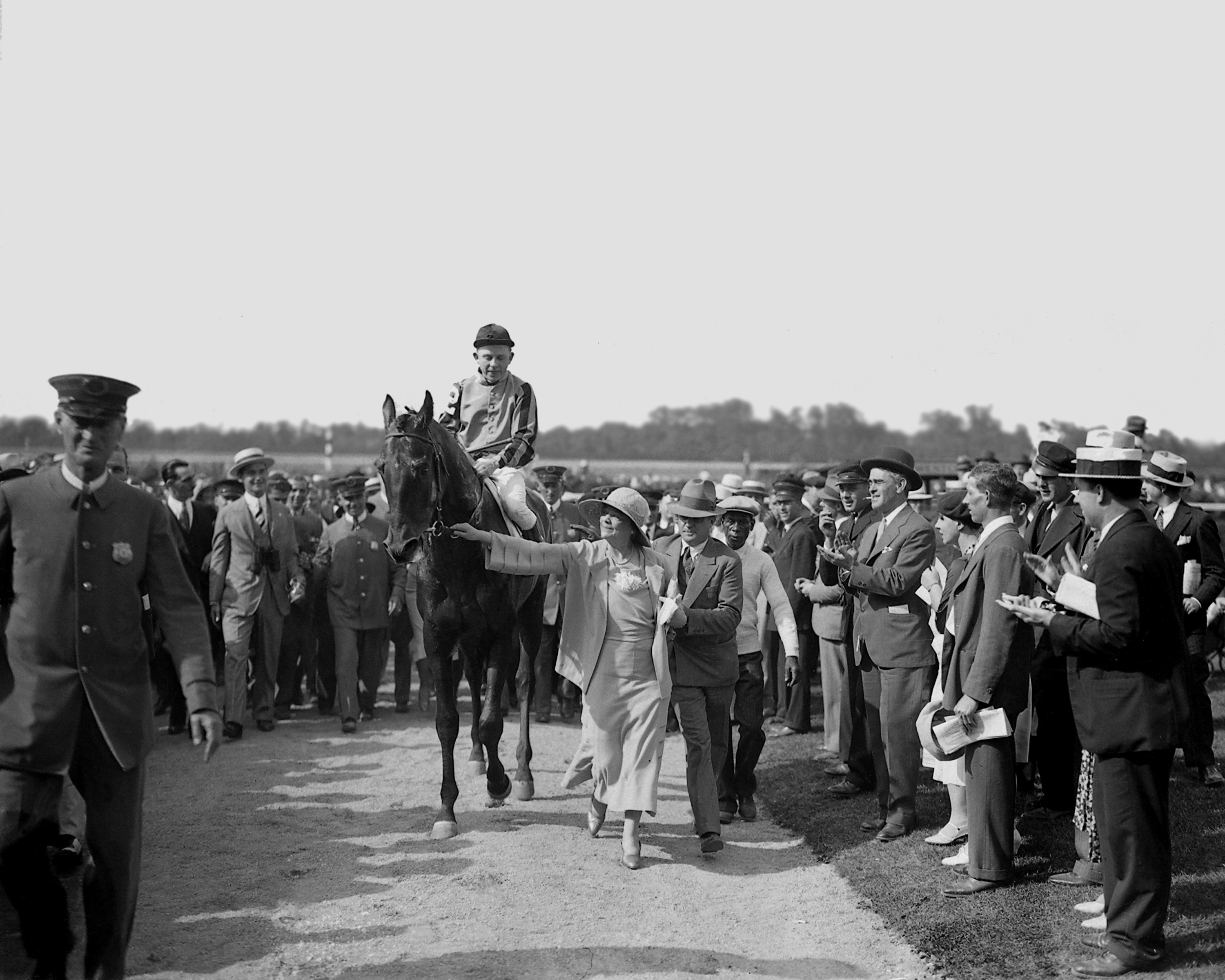 Twenty Grand (Charles Kurtsinger up) being led in by his owner, Helen Hay Whitney (Keeneland Library Cook Collection)