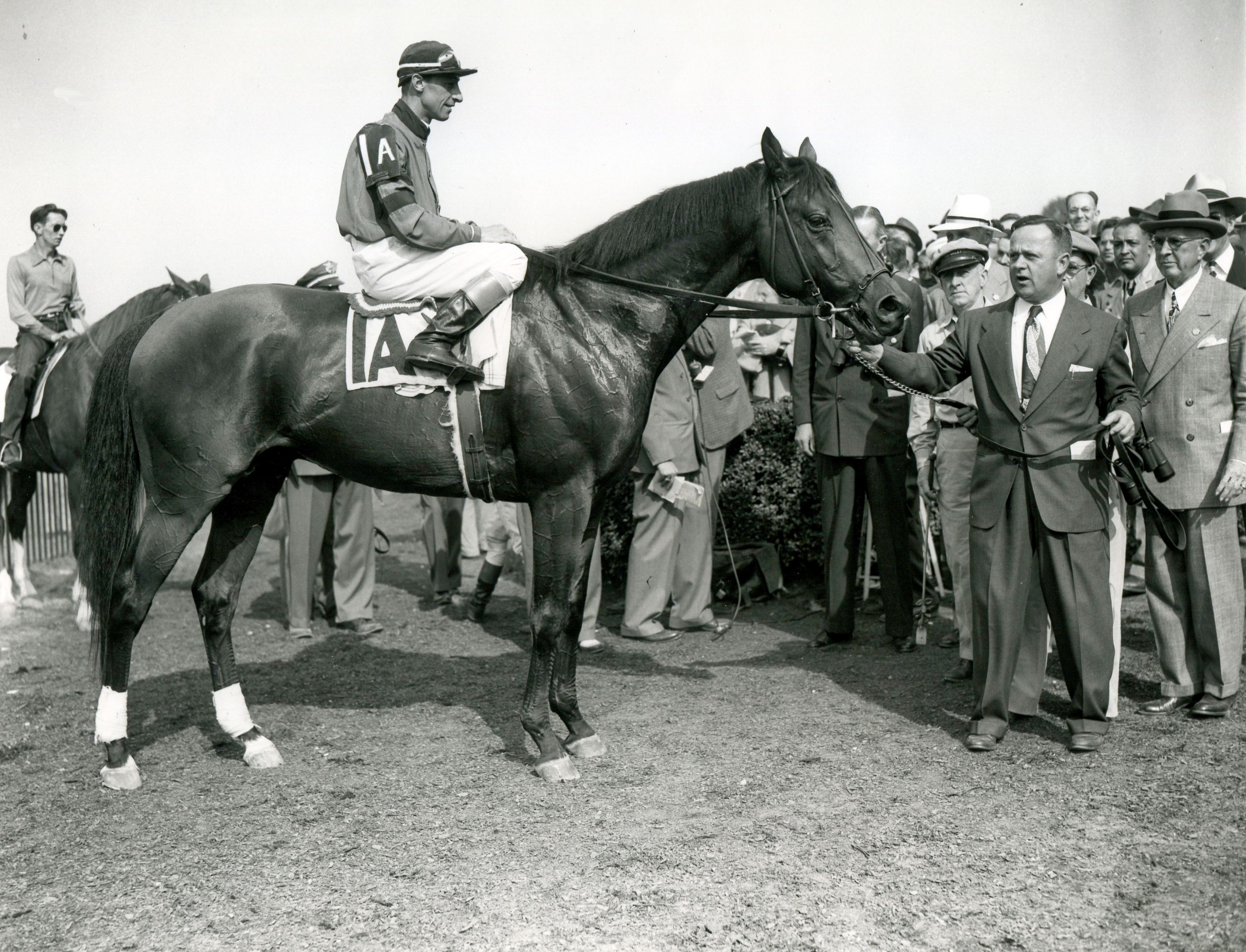 """Citation (Eddie Arcaro up) being held by trainer Horace A. """"Jimmy"""" Jones after winning the 1948 Belmont Stakes (Keeneland Library Morgan Collection/Museum Collection)"""