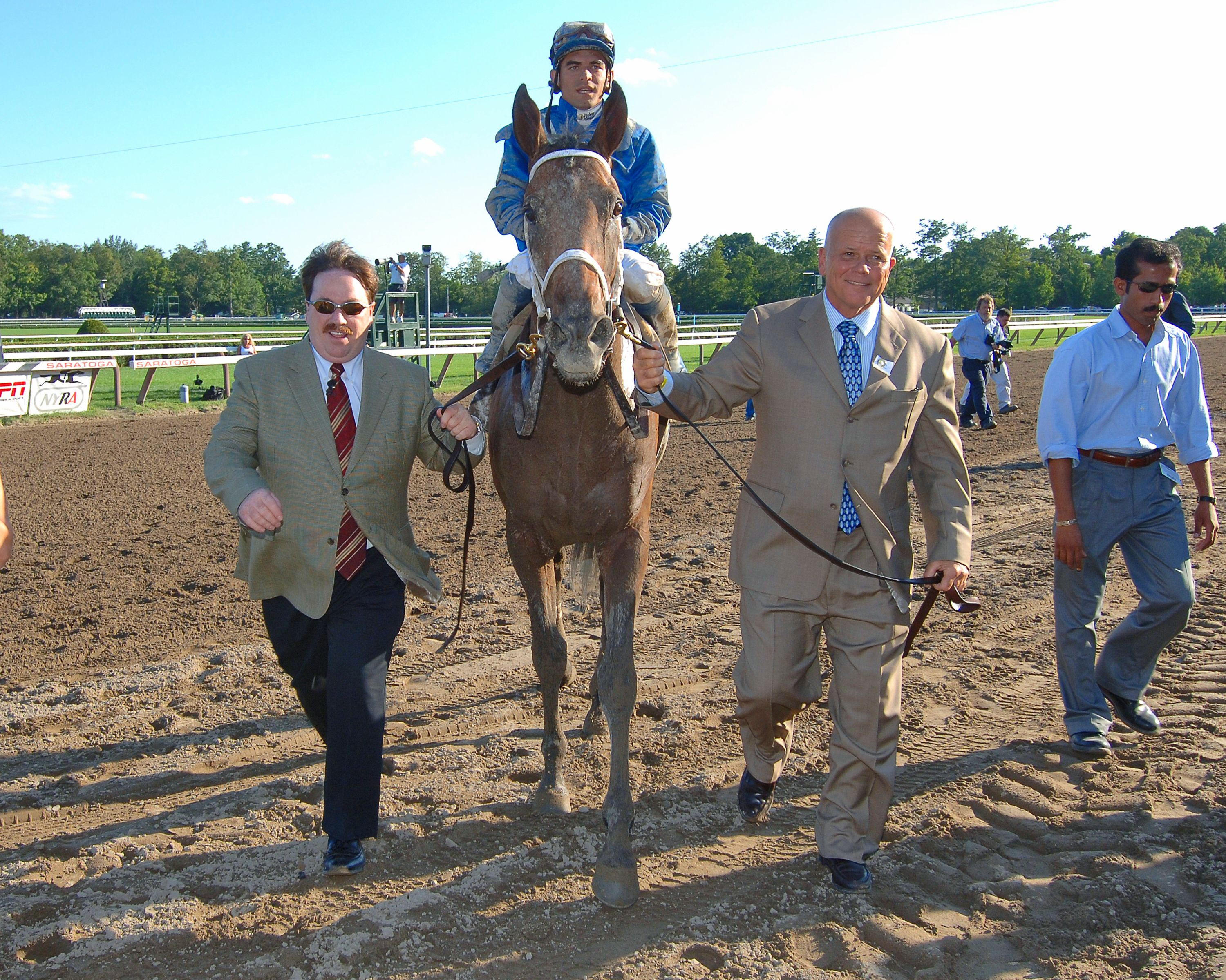 Invasor (Fernando Jara up) entering the winner's circle for the 2006 Whitney with Kiaran McLaughlin (left) and Rick Nichols (right) (NYRA)