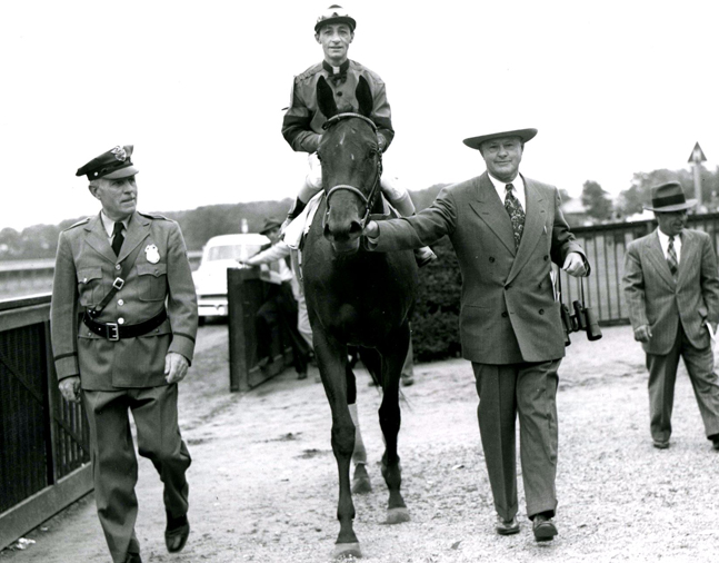 Real Delight (Eddie Arcaro up) entering the Belmont Park winner's circle at the 1952 Coaching Club American Oaks with trainer Ben Jones (Keeneland Library Morgan Collection/Museum Collection)