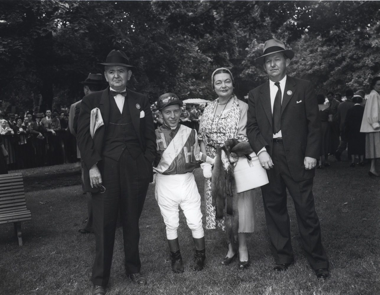 John Adams with owners Mr. and Mrs. A. E. Reuben and trainer Harry Trotsek (far right) in the Belmont Park paddock, May 1954 (Keeneland Library Morgan Collection/Museum Collection)