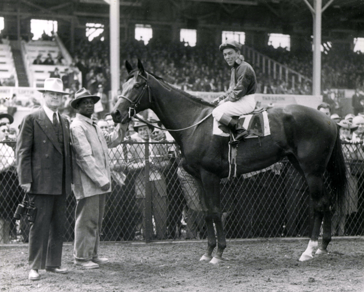 Conn McCreary and Twlight Tear in the winner's circle with trainer Ben Jones after winning the 1944 Rennert Handicap at Pimlico (The BloodHorse/Museum Collection)