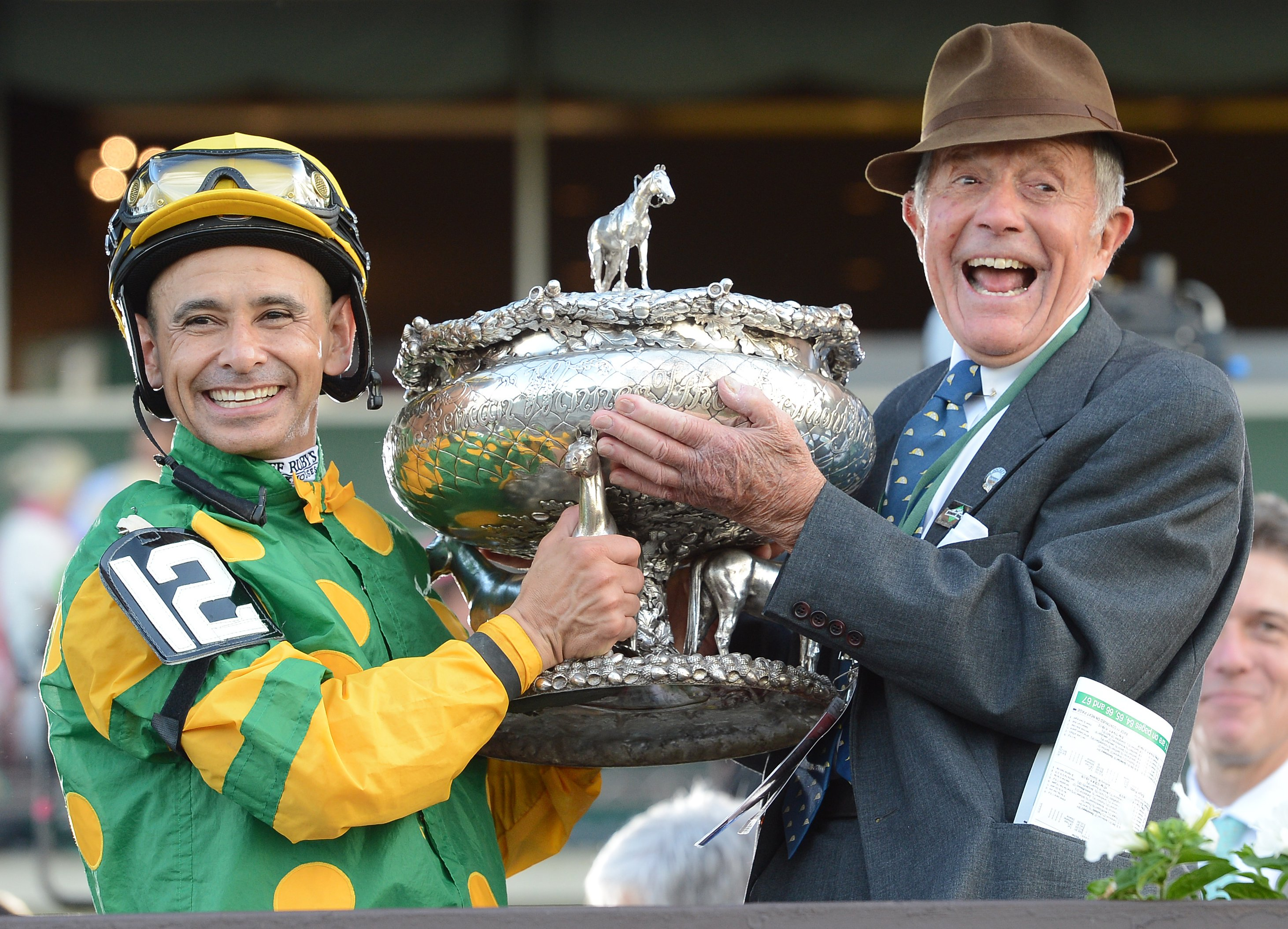 Mike Smith and Cot Campbell raise the August Belmont Memorial Trophy in celebration of Palace Malice's 2013 Belmont Stakes victory (NYRA)