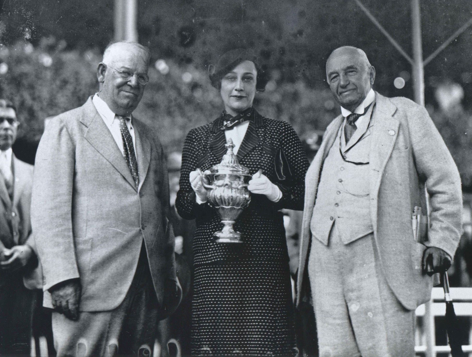 Trainer Robert Smith and owner Isabel Dodge Sloane receive the 1934 Sanford Stakes trophy for Psychic Bid from John Sanford at Saratoga (Keeneland Library Cook Collection/Museum Collection)