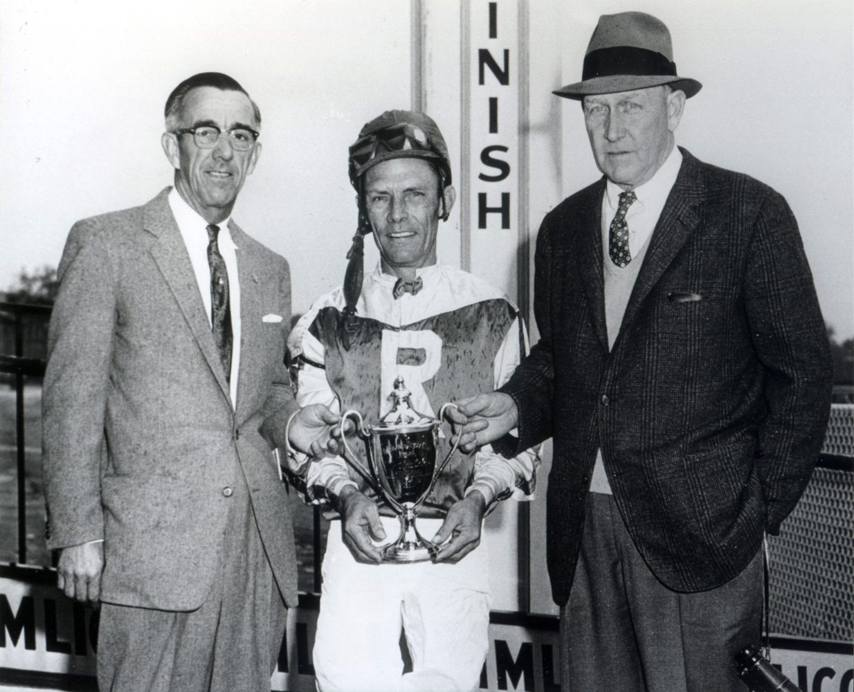 Owner L. H. Hunt, jockey Bobby Baird, and trainer Henry Clark accepting a trophy at Pimlico in 1963 (BloodHorse/Museum Collection)