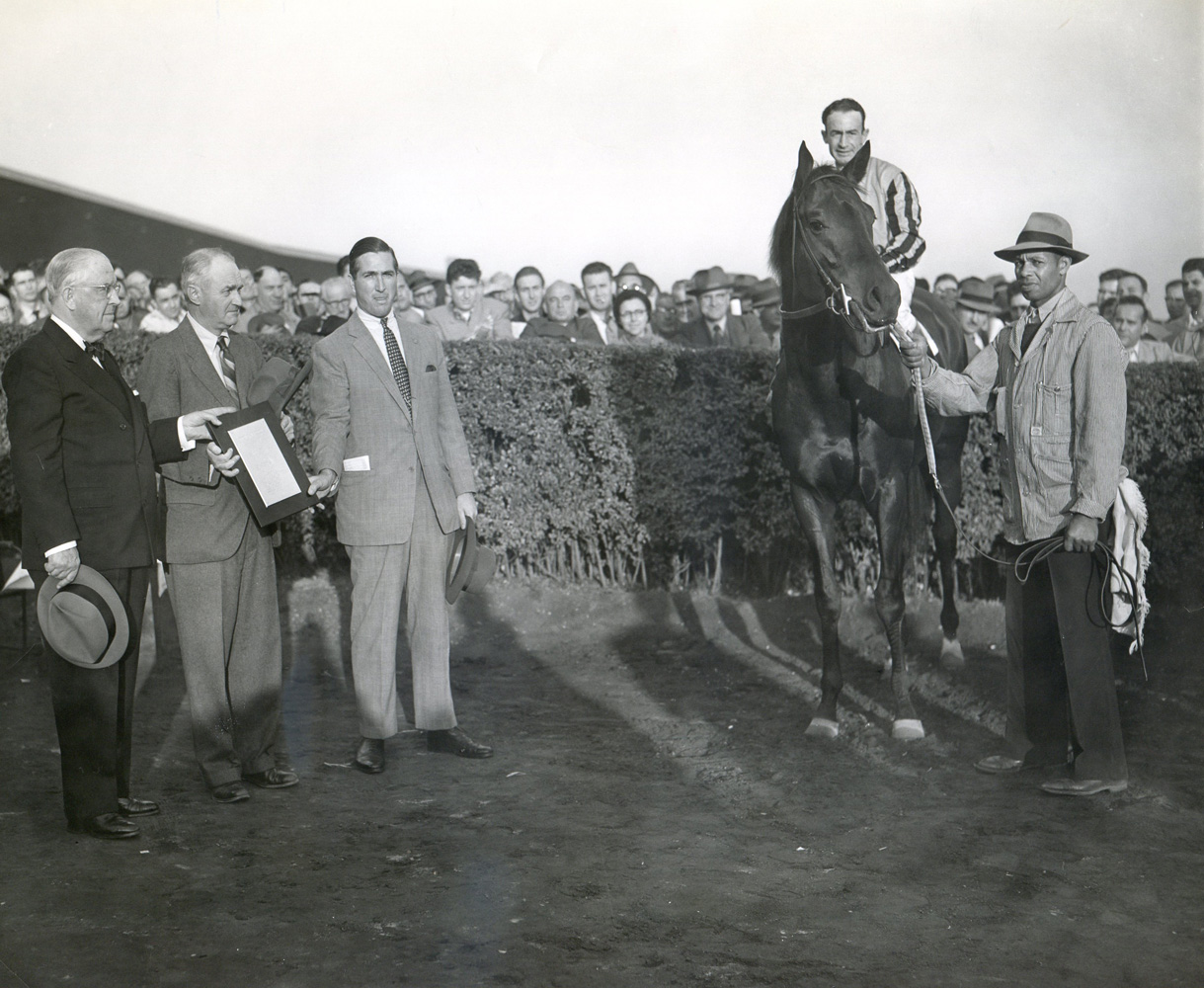 """Tom Fool (Ted Atkinson up), Ashley T. Cole, trainer John M. Gaver, Sr., and James Butler  in the winner's circle at Empire City  for his """"farewell to the turf"""" in November 1953 (Empire City Photo/Museum Collection)"""