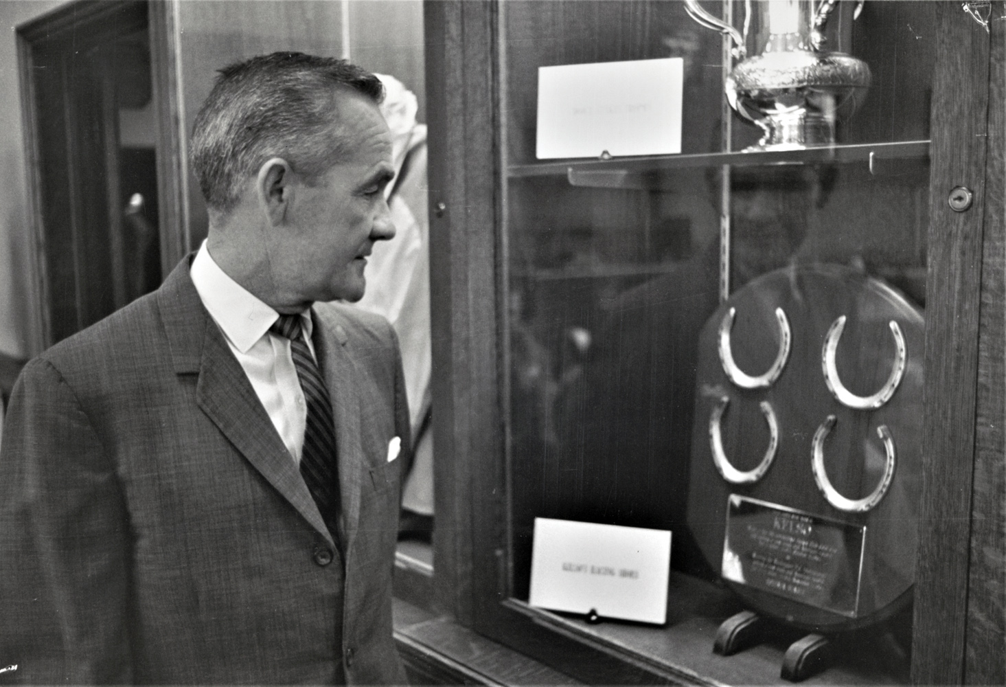 Carl Hanford looks at a display of Kelso's horseshoes and trophies (Keeneland Library Thoroughbred Times Collection)