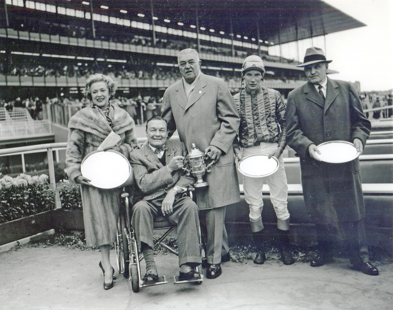 """Mr. and Mrs. Stephen """"Laddie"""" Sanford, S. Bryce Wing, jockey Thomas Walsh, and trainer Hollie Hughes at the 1959 Grand National Steeplechase trophy presentation (won by Sun Dog) (Keeneland Library Morgan Collection/Museum Collection)"""