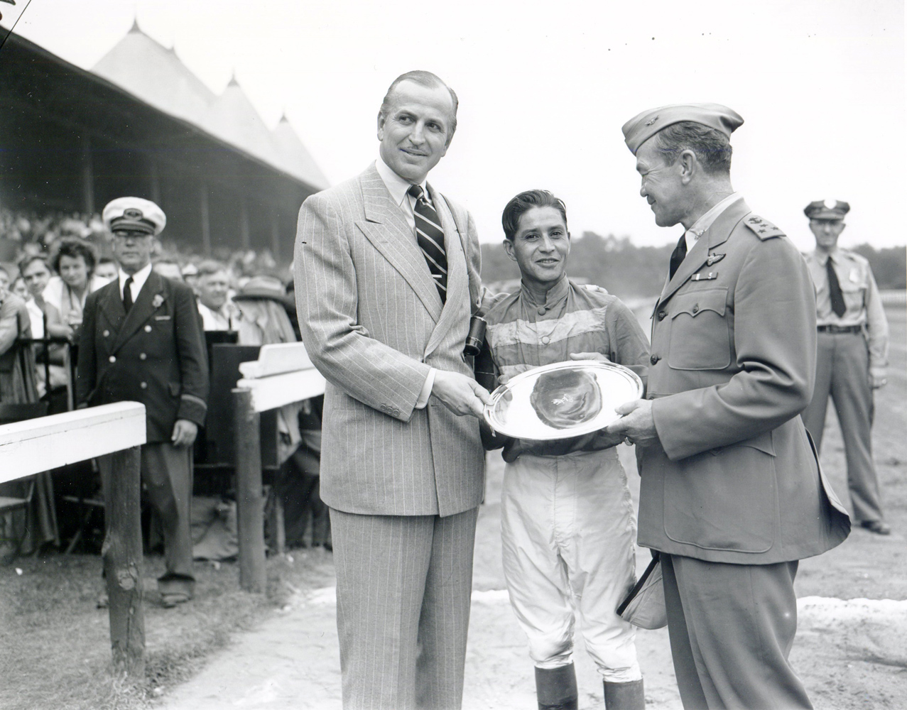Trainer Horatio Luro, jockey Ruperto Donoso, and Vice Admiral Gerald F. Bogan at the trophy presentation from the 1947 Whitney (won by Rico Monte) at Saratoga (Keeneland Library Morgan Collection/Museum Collection)