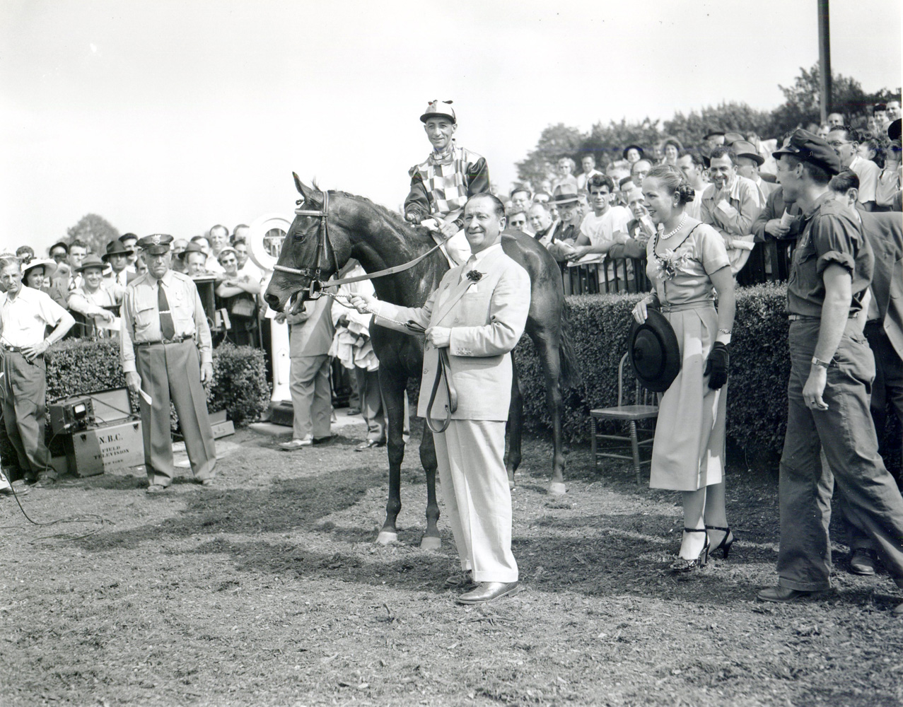 Horatio Luro holding How (Eddie Arcaro up) in the winner's circle for the 1951 Coaching Club American Oaks at Belmont Park (Keeneland Library Morgan Collection/Museum Collection)