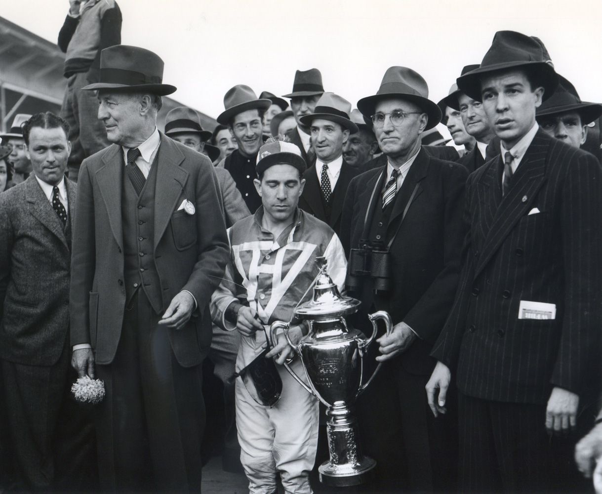 George Woolf and Tom Smith hold the Pimlico Special trophy with Alfred G. Vanderbilt on the right and owner Charles S. Howard on the left (Keeneland Library Morgan Collection/Museum Collection)